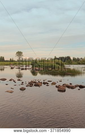 A Peaceful Evening By A River At The Northern Finland. The Sun Is Beginning To Set In The Background