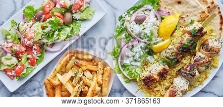 greek meal with chicken souvlaki, fries and salad