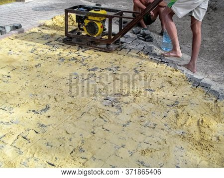 Workers Tamping A New Laid Paving Slab With A Self-production Vibrating Plate. The Process Of Instal