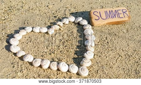 Heart-shaped Snail Shells On The Sand. The Words