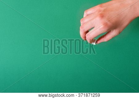 Female Hand Holds A White Dice On A Green Background. Idea For Gambling, Casino, Dice Games