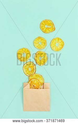Healthy Snack. Homemade Dehydrated Fruit Chips Of Tangerine On Blue Background. Dry Tangerine In Pap