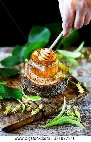 Selective Focus. Macro. Stick For Honey With Linden Honey. Linden Honey In A Jar. Leaves And Flowers