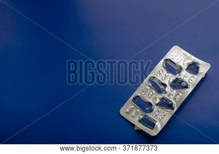 Blank Blister Of Medical Pills On A Blue Background. Seven Empty Cells In A Blister. Medical Theme B