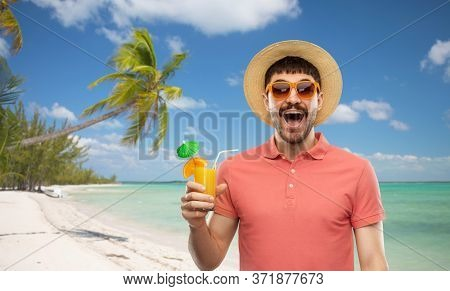 summer holidays, vacation and travel concept - happy smiling young man in sunglasses and straw hat with orange juice cocktail over tropical beach background in french polynesia