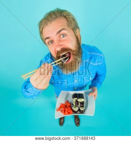 Man Eating Sushi. Sushi. Man With Sushi In Chopstick. Japan. Sushi Delivery. Japanese Food. Pickled