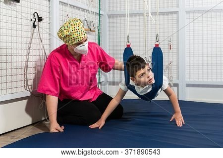 Disabled Caucasian Child Doing Physiotherapy Rehabilitation On Elastic Cords With Physiotherapist, O