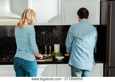 View Of Couple Cooking Fresh Salad On Kitchen Worktop