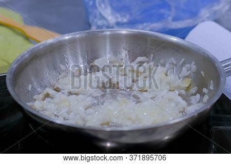 Process Of Cooking Sliced Onions In Frying Pan With Oil On Electric Stove. Professional Cooking, Cat