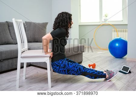 Young Woman Exercise At Home. Sporty Healthy Lifestyle. Woman Using A Chair While Doing Workout. Gir