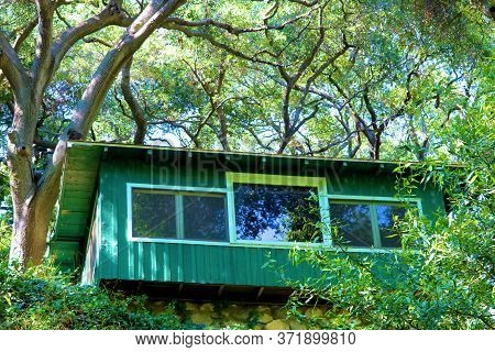 Rustic Vacation Cabin On Top Of A Hillside Overlooking A Lush Green Deciduous Forest