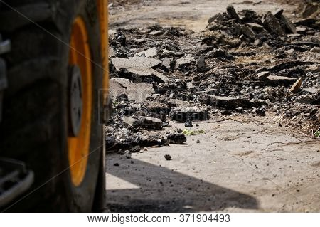 Dismantled And Broken Asphalt On A City Street Next To The Wheel Of A Yellow Construction Vehicle Or