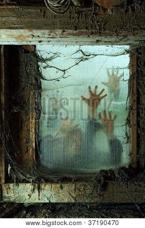 Photo of zombies outside a window that is covered with spiderwebs and filth. poster