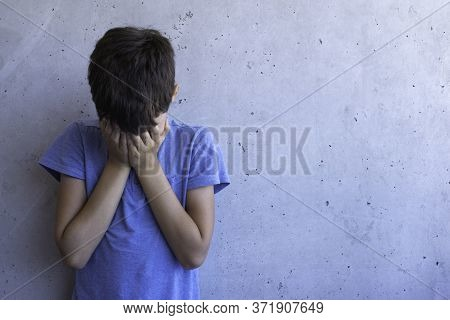 Upset Sad Boy Stand Alone And Leaning On Gray Wall. Learning Difficulties, Family Problems, Bullying