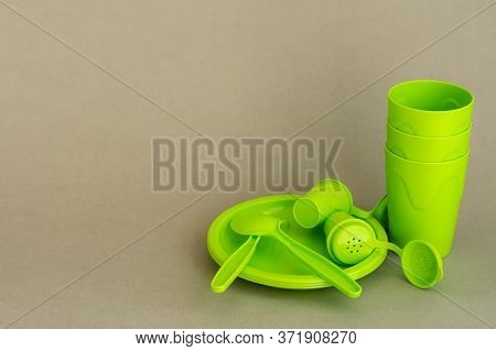 Green Plastic Tableware On A Gray Neutral Background. A Set Of Reusable Plastic Picnic Dishes. Envir