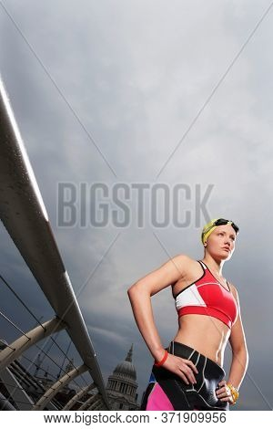 Female swimmer standing on foot bridge low angle view Millennium Bridge London England