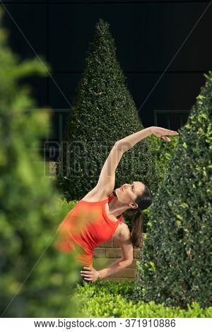 Woman stretching in landscaped garden