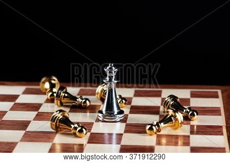 Silver Queen Chess Defeats Gold Pawns On Wooden Chessboard. Intellectual Duel And Tactical Battle In