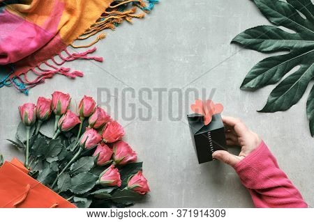 Flat Lay, Still Life With Bunch Of Rose Flowers And Exotic Plant Leaf. Hand Holding Small Gift Box W