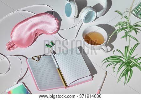 Healthy Night Sleep Creative Concept In Pink And Green. Sleep Mask, Earphones, Tea, Sleeping Pills,