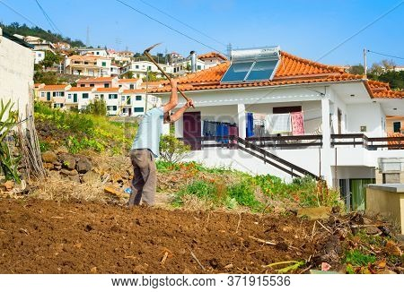 Madeira Island, Portugal - January 15, 2020: Man Working On A Field. Typical Madeira Village Archite