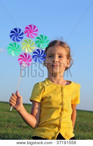 Happy little girl with whirligig sits at green grass at background of blue sky.