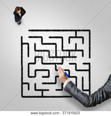 Top View Of Puzzled Businesswoman Looking At Drawn Maze On Floor