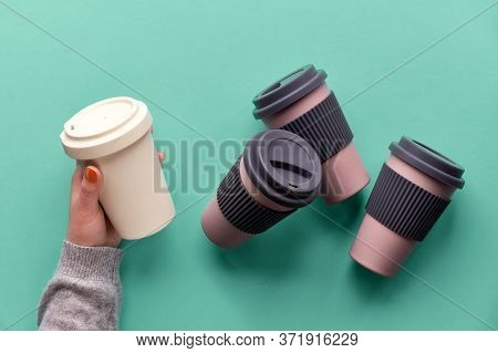 Bamboo Coffee Cups, Keep Cups Or Travel Mugs In Female Hand On Blue Mint Background. Creative Flat L