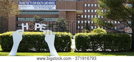 West Islip, New York, Usa - 13 May 2020: Wooden Sign Of Hands Holding The Words Hope Placed Infront