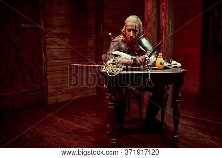 A medieval warrior in armor and with weapons is resting in the inn. Stage portrait. The Witcher man.