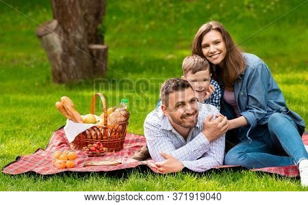 Summertime Family Activities. Joyful Parents With Son Enjoying Their Picnic Outdoors, Copy Space. Pa
