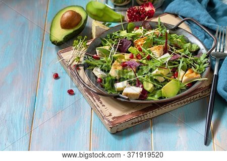 Arugula Salad With Chicken, Avocado, Pomegranate And Cheese On Wooden Table. Copy Space.