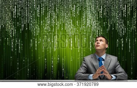 Man With Folded Hands Looking Upward. Young Businessman Sitting At Desk. Programmer Wears Business S