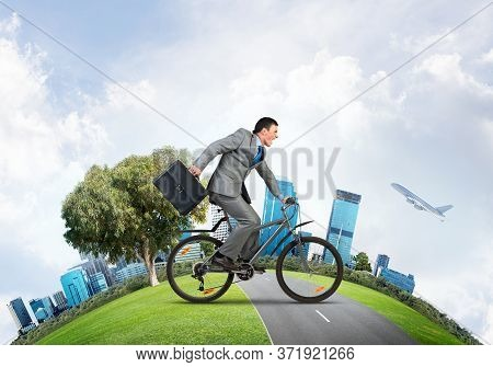 Young Man Riding Bicycle On Road. Businessman On Bike Hurry To Work. Corporate Employee Wearing Busi
