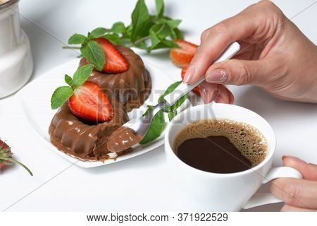 Woman Eats Dessert. Chocolate Fudge Garnished With Half A Strawberry With Petals. Garnished With Spr
