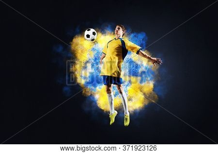 Soccer Player Jumping With Ball In Smoke. Sportsman In Yellow And Blue Uniform In Action. Soccer Gam