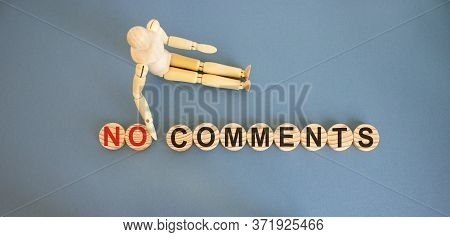 Wooden Circles With Words 'no Comments'. Concept. Wooden Model Of A Person Pushing Back The Word 'no