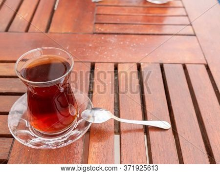 Turkish Black Tea Glass With Teaspoon On The Wooden Table. Turkish Traditional Drink.