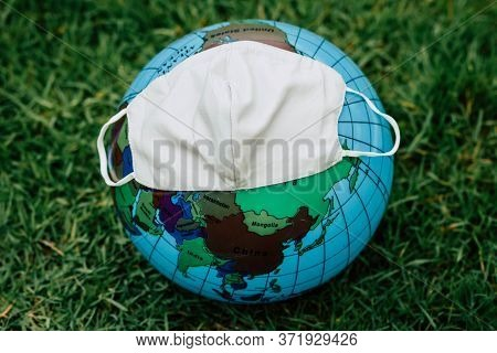 Globe Sphere Orb Model Effigy. Put On A Surgical Mask. Placed In A Green Lawn.conceptual Picture Of