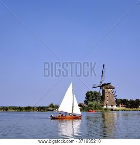 Bleiswijk,holland-august 10,2019: Sailing Boat In Front Of Windmill On The River Rotte Near Bleiswij