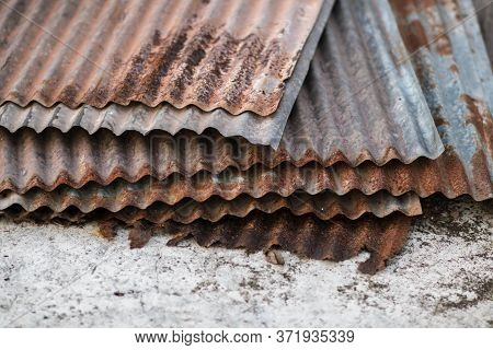 Sharp Edges Of The Rusty Metal Sheets Placed On The Floor. Old Aged Weathered Rusty Galvanized Corru