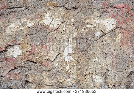 Fragment Of An Old Weathered Stone Wall With Cracks And Chips. Partially Chipped Plaster