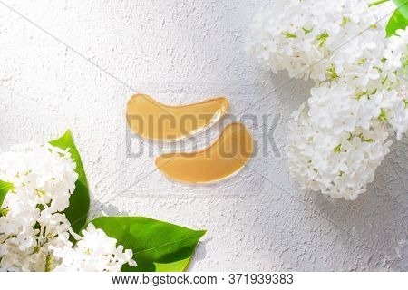 Hydrogel Yellow Patches Under The Eyes And Flowers. Lilac Flowers. Light Background. Space For The T