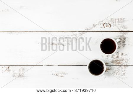 Two Mugs Of Black Coffee Or Espresso On A White Wooden Table Background. The Concept Of Caffeine In
