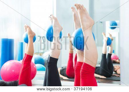Pés de mulheres de pilates aeróbica com bolas de ioga em uma linha na classe de aptidão