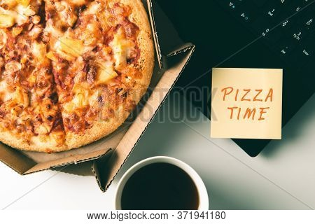 Pizza In Box, Cup Of Coffee, Laptop And Sticker With Text Pizza Time On Desk In Office. Concept Of F