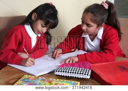 Two Siblings Doing School Work From Home Together In Oxford, Oxfordshire, Uk. Taken On 01 28 2011