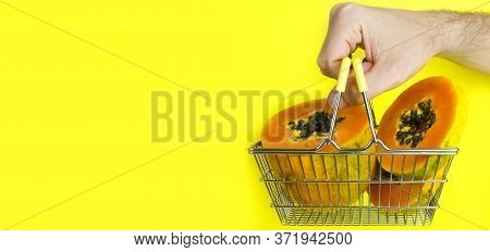 Shopping Basket With Tropical Fruit Papaya And Man Hand Holding The Basket On Yellow Background. Sho