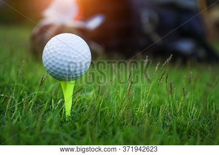 Golf Ball On Tee Ready To Be Shot. Golf Ball On Tee In The Evening Golf Course With Sunshine.
