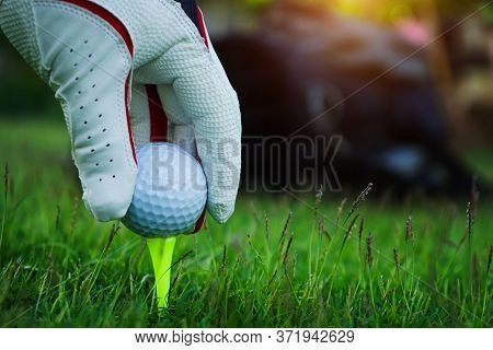 Golf Glove Hand Hold Golf Ball With The Tee On A Beautiful Golf Course With Golf Bag And Green Grass